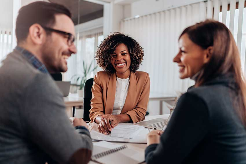 One businessman & one businesswoman looking at each other and smiling, one businesswoman is also looking at them and smiling - Greenberg Financial Group
