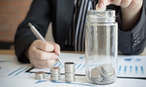 A person putting a coin in a jar and writing with other hand - Greenberg Financial Group