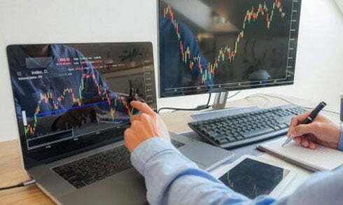 Market Trends are showing at computer screen pointing by a businessman- Greenberg Financial Group