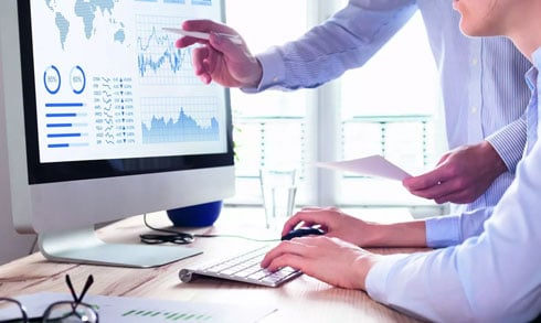 Market Trends are showing at computer screen pointing by a businessman to the other one – Greenberg Financial Group