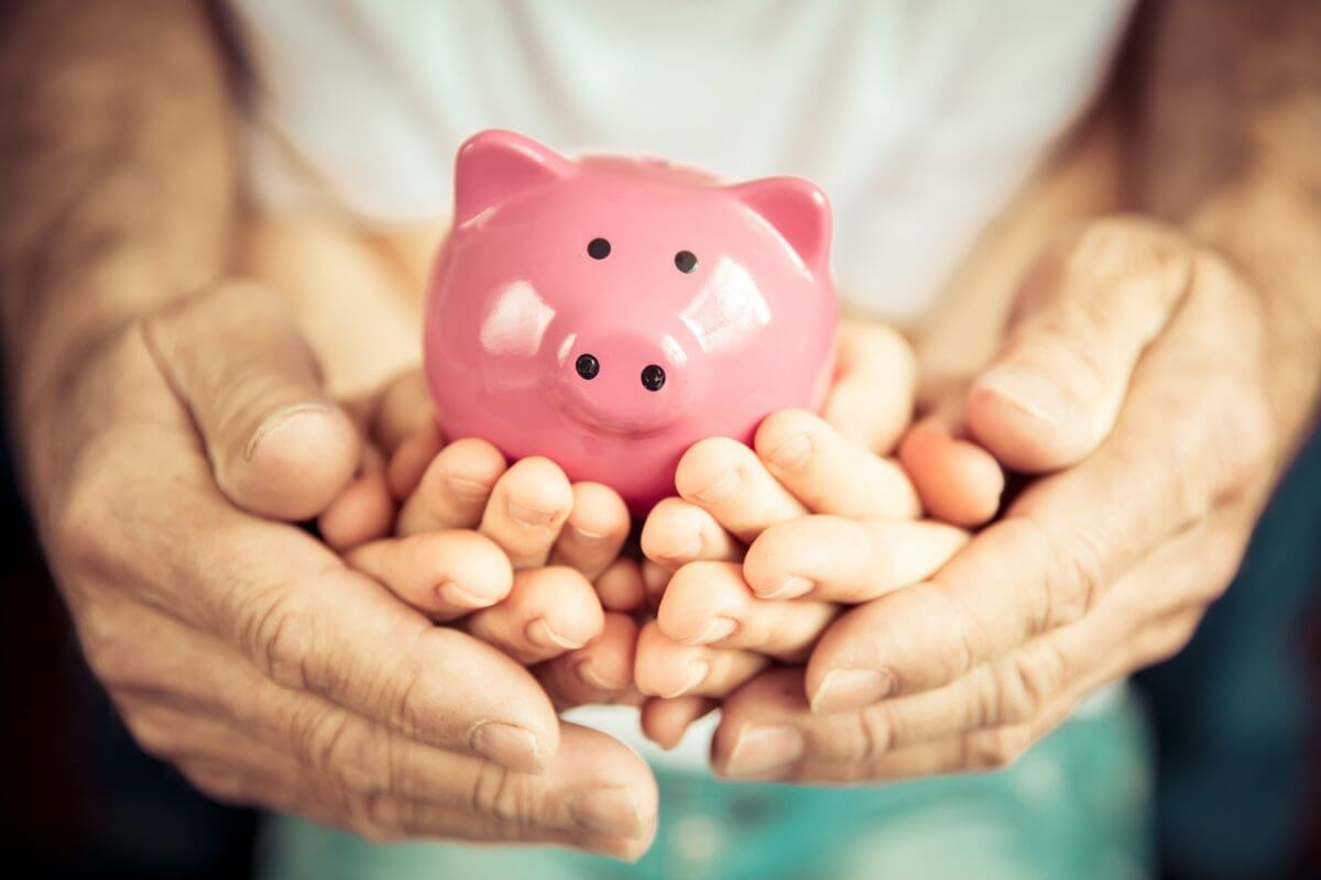 A man holding hand of his children and their hand are holding piggy bank - Greenberg Financial Group