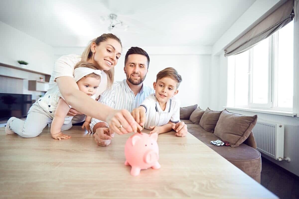 A family saving money in piggy bank- Greenberg Financial Group