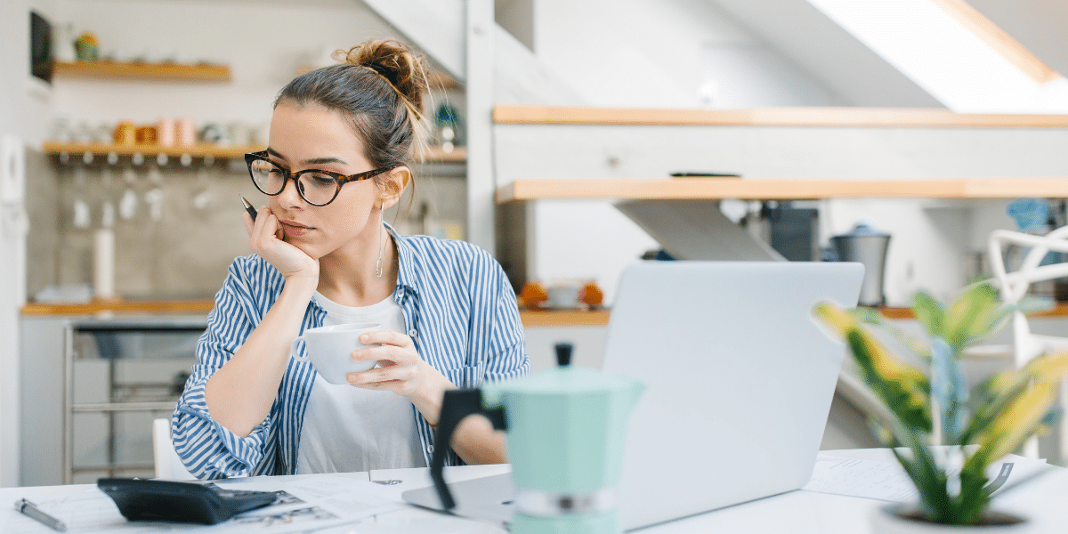 Young woman sits in front of laptop with cup of coffee